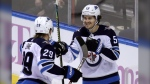 Winnipeg Jets center Mark Scheifele (55) is congratulated by right wing Patrik Laine (29) after scoring a goal against the Florida Panthers during the third period of an NHL hockey game, Thursday, Nov. 14, 2019, in Sunrise, Fla. (Source: AP Photo/Lynne Sladky)
