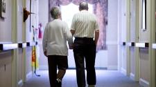 In this Nov. 6, 2015 file photo, an elderly couple walks down a hall in Easton, Pa. (AP Photo/Matt Rourke, File)