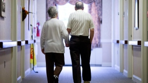 In this Nov. 6, 2015 file photo, an elderly couple walks down a hall in Easton, Pa. (AP Photo/Matt Rourke, File)