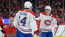 Montreal Canadiens center Nick Suzuki (14) celebrates his goal with right wing Brendan Gallagher, right, during the second period of an NHL hockey game, against Washington Capitals goaltender Ilya Samsonov, lower left, Friday, Nov. 15, 2019, in Washington. (AP Photo/Nick Wass)