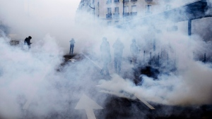 Tear gas envelopes protesters during a yellow vest demonstration marking the first anniversary in Paris, Saturday, Nov. 16, 2019. (AP Photo/Kamil Zihnioglu)