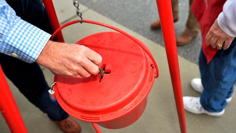 In this Nov. 9, 2018, file photo money gets dropped into the kettle during the annual Salvation Army Kettle campaign kick off in Augusta, Ga. (THE CANADIAN PRESS/Michael Holahan/The Augusta Chronicle via AP)