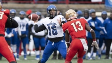 Montreal Carabins' Frederic Paquette-Perrault (16) throws under pressure from Laval Rouge et Or's Souleymane Karamoko (13) during first half USports Dunsmore Cup university football action in Quebec City, Saturday, Nov. 9, 2019. THE CANADIAN PRESS/Jacques Boissinot