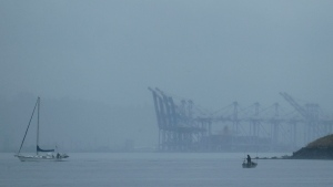 With cranes from the Port of Tacoma in the background, a man fishes from a boat on the waters of Puget Sound near Owen Beach Wednesday, July 10, 2019, in Tacoma, Wash. (AP Photo/Ted S. Warren)