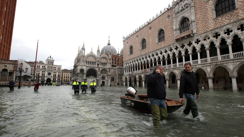 People drag a small boat in a flooded St. Mark square in Venice, Italy, Sunday, Nov. 17, 2019. (AP Photo/Luca Bruno)