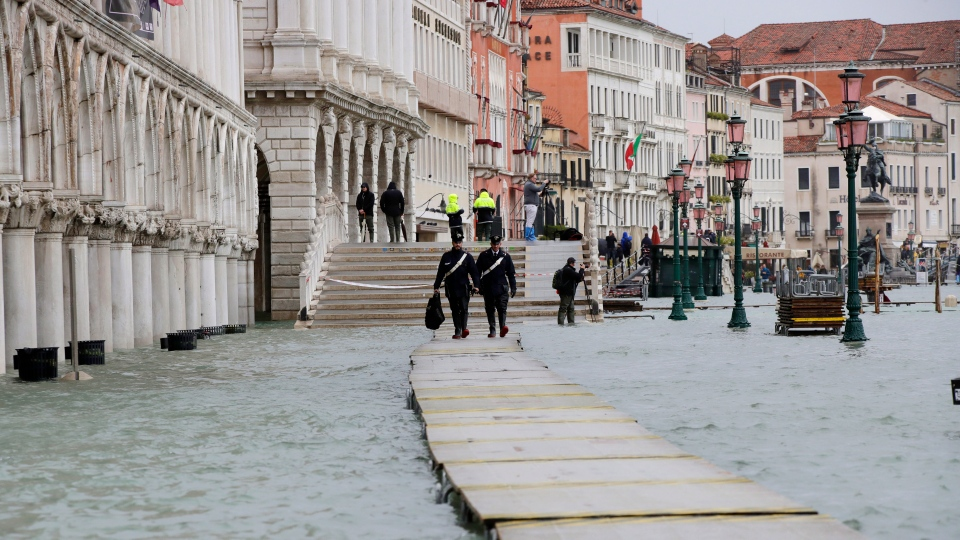 Two Carabinieri walk on a gangway in flooded Venice, Italy, Sunday, Nov. 17, 2019. (AP Photo/Luca Bruno)