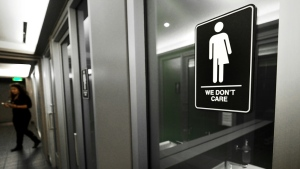 Gender-neutral signs are posted in public restrooms in a hotel in Durham, N.C. in May 2016  (AFP)