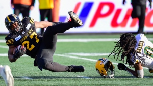 Edmonton Eskimos linebacker Don Unamba (0) loses his helmet after hitting Hamilton Tiger-Cats running back Cameron Marshall (27) during second half CFL East Final football action in Hamilton, Ont., on Sunday, Nov. 17, 2019. (THE CANADIAN PRESS/Frank Gunn)