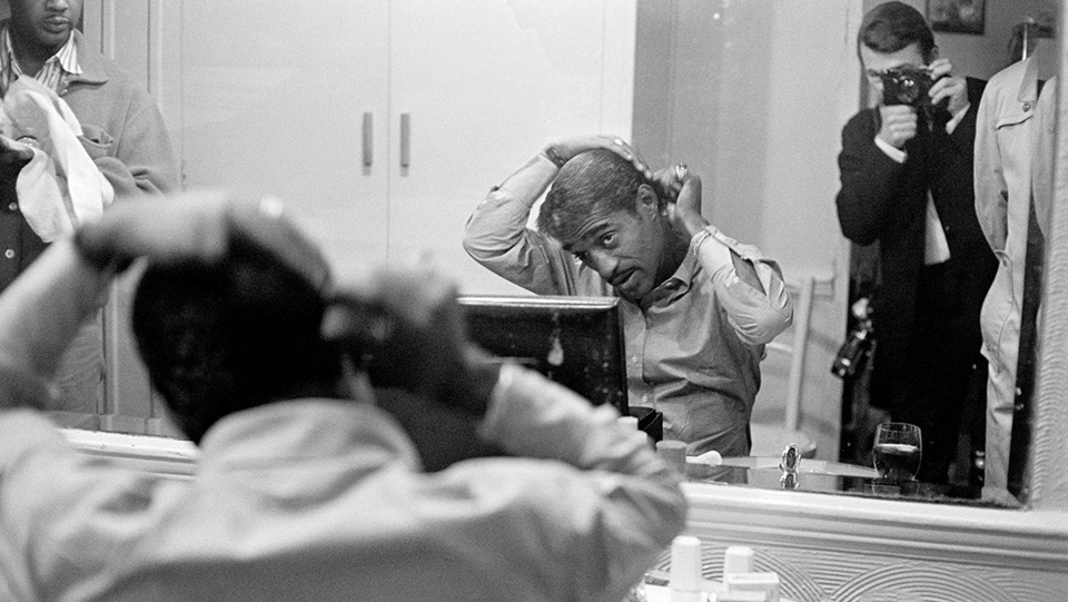Sammy Davis Jr gets ready for a show backstage at a venue in London, 1961. (Terry O'Neill/Iconic Images)