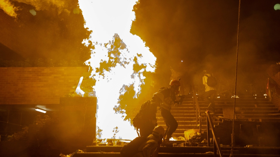 A fire burns near the campus of Hong Kong Polytechnic University in Hong Kong, early Monday, Nov. 18, 2019. Police stormed into a Hong Kong university campus held by protesters early Monday after an all-night siege that included firing repeated barrages of tear gas and water cannons. (AP Photo/Vincent Yu)