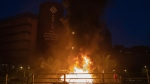 A fire burns as police storm part of the Hong Kong Polytechnic University campus during the early morning hours in Hong Kong, Monday, Nov. 18, 2019. Police breached the university campus held by protesters early Monday after an all-night siege that included firing repeated barrages of tear gas and water cannons. (AP Photo/Ng Han Guan)