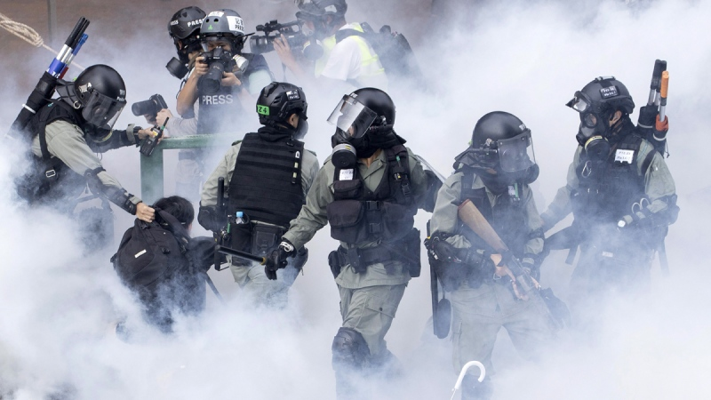 Police in riot gear move through a cloud of smoke as they detain a protester at the Hong Kong Polytechnic University, on Nov. 18, 2019. (Ng Han Guan / AP)