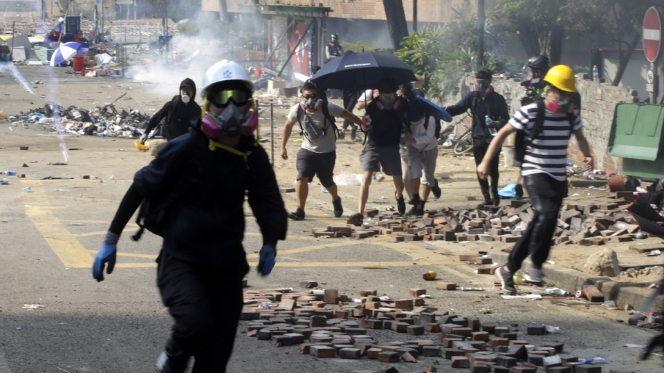 Protesters run as police fire tear gas