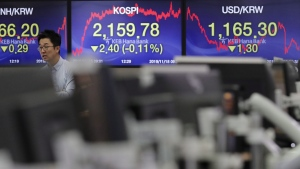 A currency trader walks near screens showing the Korea Composite Stock Price Index (KOSPI), centre, and the foreign exchange rate between U.S. dollar and South Korean won, right, at the foreign exchange dealing room in Seoul, South Korea, on Nov. 18, 2019.  (Lee Jin-man / AP)