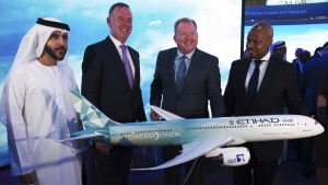 Etihad COO Mohammad al-Bulooki, left, Etihad CEO Tony Douglas, second left, Boeing Commercial Airplanes president and CEO Stanley A. Deal, third left, and Boeing Global Services President and CEO Ted Colbert, right, pose in front of a Boeing 787 Dreamliner model at the Dubai Airshow in Dubai, United Arab Emirates, on Nov. 18, 2019. (Jon Gambrell / AP)