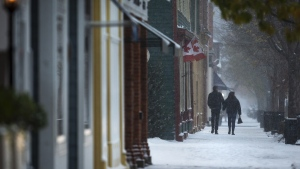 Pedestrians walk through snow along Queen Street in Niagara-on-the-Lake, Ont., on Nov. 11, 2019. (Tara Walton / THE CANADIAN PRESS)