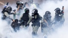 Police in riot gear move through a cloud of smoke as they detain a protester at the Hong Kong Polytechnic University in Hong Kong, Monday, Nov. 18, 2019. Hong Kong police fought off protesters with tear gas and batons Monday as they tried to break through a police cordon that is trapping hundreds of them on a university campus. (AP Photo/Ng Han Guan)