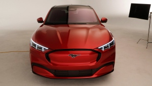 In this Wednesday, Oct. 30, 2019 photo, the front of the new Ford Mustang Mach-E SUV is shown in Warren, Mich. Ford is hoping to score big with the electric SUV for daily drivers that sort of looks like a Mustang performance car. The new SUV, to be unveiled just ahead of the Los Angeles Auto Show press days, should have range of up to 300 miles. It's one of dozens of electric vehicles coming globally by 2022. Automakers are eyeing what they think will be a growing market in the years to come. (AP Photo/Carlos Osorio)