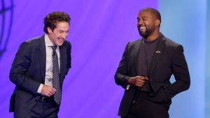With their eyes closed for prayer, Joel Osteen, left, and Kanye West laugh as West makes a joke while leading the prayer during a service at Lakewood Church, Sunday, Nov. 17, 2019, in Houston. (AP Photo/Michael Wyke)