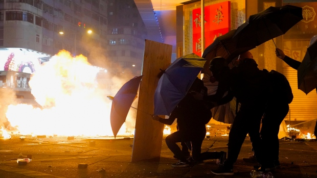 Protesters cover with umbrellas from tear gas canister in the Kowloon area of Hong Kong, Monday, Nov. 18, 2019. (AP Photo/Vincent Yu)