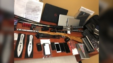 RCMP seize a number of knives, swords, ammunition, a rifle, notebooks, computers, and cellphones in the RM of Fisher, Man., after threats were made against officers on social media. (Source: RCMP)