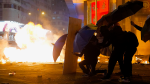 Protesters take cover from a tear gas canister under umbrellas in the Kowloon area of Hong Kong, Monday, Nov. 18, 2019. ( AP / Vincent Yu)