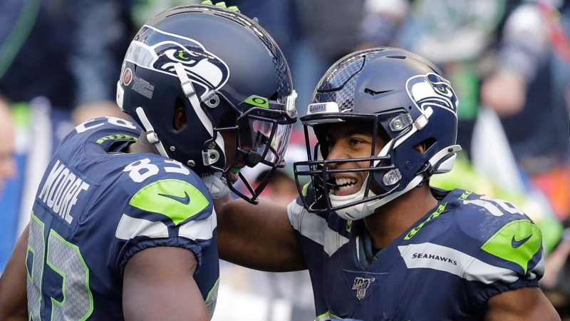Seattle Seahawks wide receiver Tyler Lockett, right, is greeted by wide receiver David Moore (83) after scoring a touchdown against the Tampa Bay Buccaneers during the second half of an NFL football game, Sunday, Nov. 3, 2019, in Seattle. (AP Photo/John Froschauer)