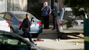 Fresno police Investigator Brooke Passmore, left, works on the driveway on Lamona Avenue where a shooting took place at a house party which involved multiple fatalities and injuries in Fresno, Calif., Monday, Nov. 18, 2019. (AP Photo/Gary Kazanjian)