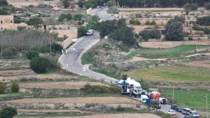 In this Oct. 19, 2017 file photo, forensic police work on the main road in Bidnija, Malta, which leads to the house of Daphne Caruana Galizia, looking for evidence on the blast that killed the investigative journalist. Maltese authorities say a man arrested in a money-laundering case claims to have information identifying the mastermind behind the car-bomb assassination of investigative journalist Daphne Caruana Galizia. (AP Photo/Rene Rossignaud)