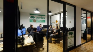 In this Monday, Nov. 4, 2019 photo, from left to right, Steve Motino, Lea Knio, Samuel Brownsword, Axel Hellman and Anthony Giordano, of OurBus, meet in their WeWork office space, in New York. WeWork is slashing the lavish spending that has fueled its breakneck growth while racking up unsustainable losses. Experts are skeptical that the office-sharing company can achieve meaningful cost reductions without somehow squeezing tenants. (AP Photo/Richard Drew)