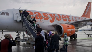 In this Thursday Oct. 18, 2012 file photo, passengers board a London-bound EasyJet flight at Amsterdam's Schiphol airport, Netherlands. European budget airline easyJet said Tuesday Nov. 19, 2019, that it will become the first major carrier to operate net-zero carbon flights, offsetting carbon emissions from the fuel used on every flight. (AP Photo/Peter Dejong, File)