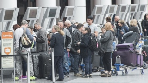 Passengers line up at a check in desk at Trudeau Airport in Montreal on March 13, 2019. THE CANADIAN PRESS/Graham Hughes