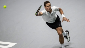 Canada's Vasek Pospisil misses a ball during the Davis Cup tennis match against USA player Reilly Opelka in Madrid, Spain, Tuesday, Nov. 19, 2019. (AP Photo/Bernat Armangue)