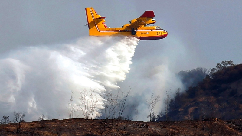 "A Bombardier CL-415 firefighting aircraft, also known as ""Super Scooper"" airplane ,makes a drop on a wildfire in the San Gabriel Mountains in Azusa, Calif., Tuesday, Sept. 24, 2013. (AP Photo/Nick Ut)"