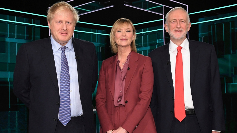This photo issued by ITV shows Boris Johnson, left, and Jeremy Corbyn, right, with TV debate adjudicator Julie Etchingham, prior to their election head-to-head debate live on TV, in Manchester, England, Tuesday, Nov. 19, 2019. (ITV via AP)