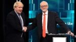In this photo issued by ITV, Boris Johnson, left, and Jeremy Corbyn, right, shake hands during their election head-to-head debate live on TV, in Manchester, England, Tuesday, Nov. 19, 2019. (ITV via AP)