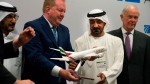Boeing Commercial Airplanes president and CEO Stanley A. Deal, left, hands Sheikh Ahmed bin Saeed Al Maktoum, the chairman and CEO of the Dubai-based long-haul carrier Emirates, a model of a Boeing 787 Dreamliner at the Dubai Airshow in Dubai, United Arab Emirates, Wednesday, Nov. 20, 2019. (AP Photo/Jon Gambrell)