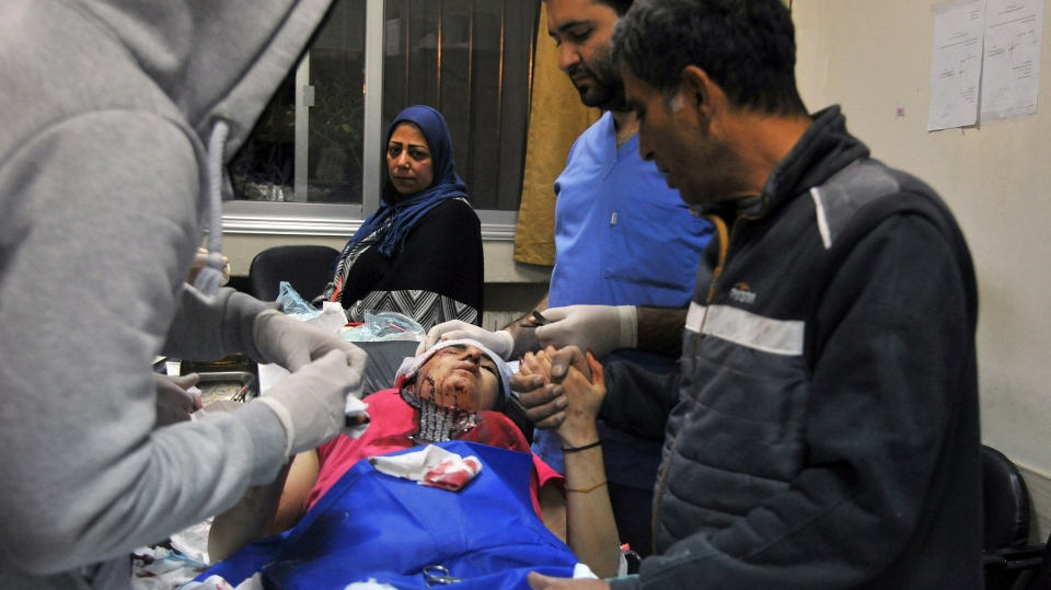 In this photo released by the Syrian official news agency SANA, a paramedic treats an injured woman wounded by Israeli missile strikes at a hospital in Damascus, Syria, Wednesday, Nov. 20, 2019. (SANA via AP)