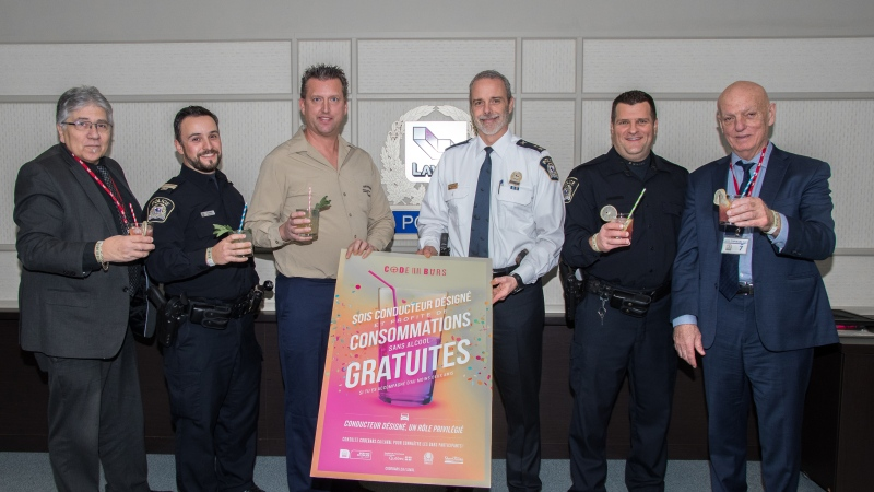 Representatives from the Laval police announce free non-alcoholic drinks for designated drivers alongside representatives of the Union of Quebec Bar Owners.