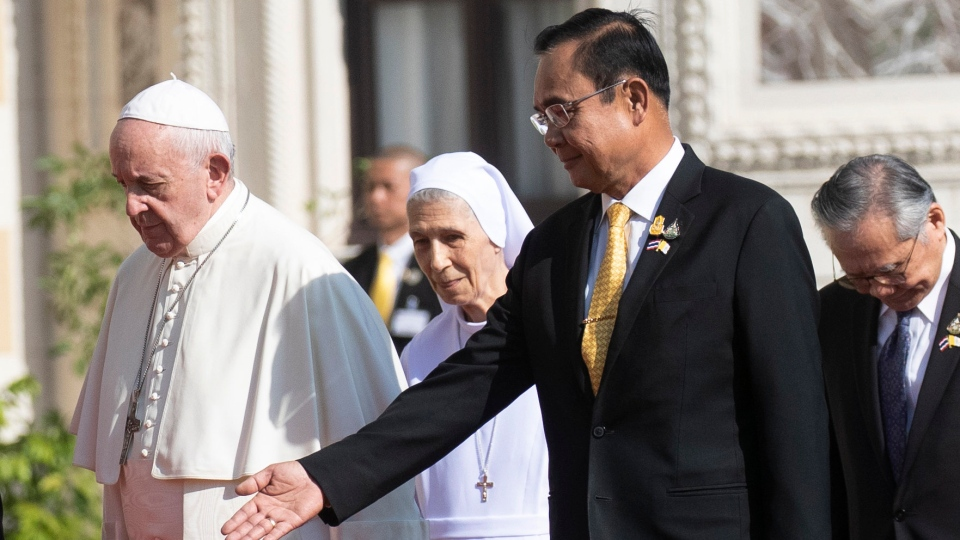 Pope Francis, left, walks with his cousin Ana Rosa Sivori, center, as Thailand's Prime Minister Prayuth Chan-ocha shows the way during a welcoming ceremony at the government house in Bangkok, Thailand, Thursday, Nov. 21, 2019. (AP Photo/Sakchai Lalit)