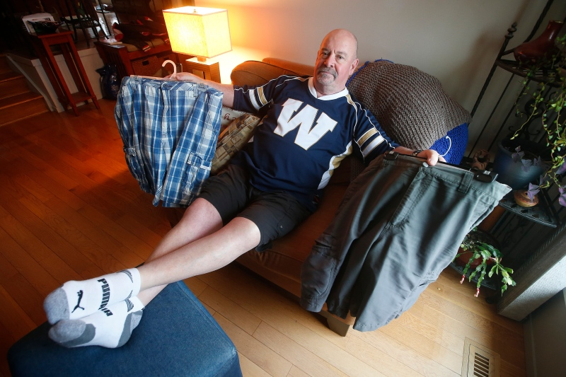 Winnipeg Blue Bomber fan Chris Matthews, who has been wearing shorts daily since the 2001 Grey Cup in Calgary, shows off some of his shorts in his living room in Winnipeg Wednesday, November 20, 2019. THE CANADIAN PRESS/John Woods