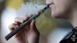 In this Oct. 4, 2019, file photo, a woman using an electronic cigarette exhales in Mayfield Heights, Ohio. (AP Photo/Tony Dejak, File)