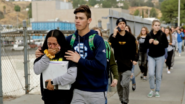 "This Nov. 14, 2019 file photo shows students being escorted out of Saugus High School after a shooting on the campus in Santa Clarita, Calif. Authorities say the teenager who shot five classmates, killing two, at a Southern California high school used an unregistered ""ghost gun."" Los Angeles County Sheriff Alex Villanueva Villanueva told media outlets Thursday, Nov. 21, 2019 that Nathaniel Tennosuke Berhow's semi-automatic handgun had been assembled and did not have a serial number. Authorities are still working to determine how Berhow got the handgun. Berhow died from a self-inflicted gunshot wound after the shooting. (AP Photo/Marcio Jose Sanchez, File)"