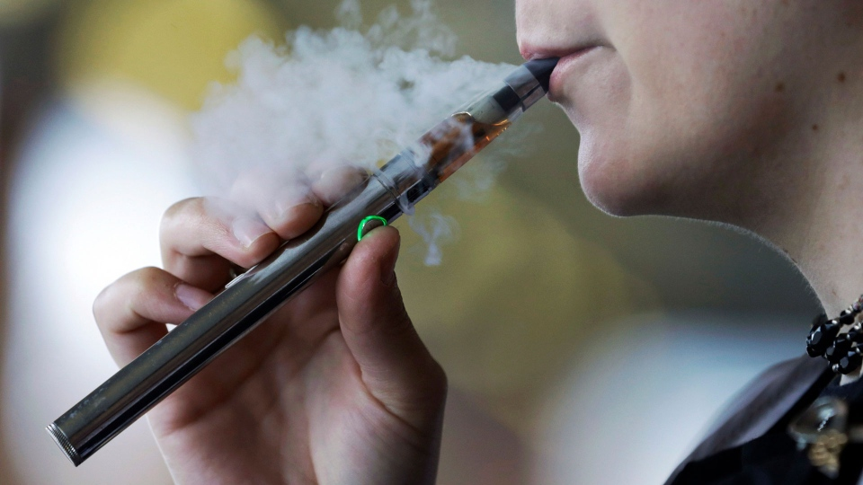 In this Oct. 4, 2019, file photo, a woman using an electronic cigarette exhales in Mayfield Heights, Ohio. (AP / Tony Dejak, File)