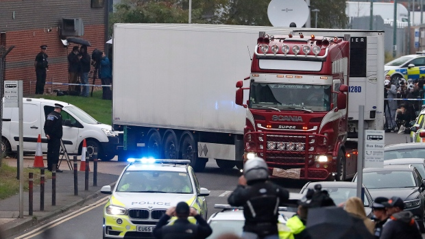 FILE - In this Wednesday Oct. 23, 2019 file photo, police escort the truck, that was found to contain a large number of dead bodies, as they move it from an industrial estate in Thurrock, south England. (AP Photo/Alastair Grant, File)