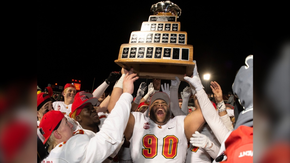 University of Calgary Dinos' J-Min Pelley raises the trophy with teammates after winning the U Sports Vanier Cup university football championship against the University of Montreal Carabins, in Quebec City on Sunday. (The Canadian Press/Jacques Boissinot)