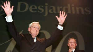 Desjardins president Claude Beland, waves to delegates following his farewell speech, as he transfers his powers to the new president Alban D'amour, right, during Desjardin's annual general meeting in Quebec City in 2000. Beland died Nov. 24, 2019. THE CANADIAN PRESS/Jacques Boissinot