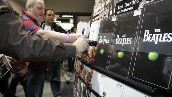 People pick up albums by The Beatles at a HMV store in London, Wednesday, Sept. 9, 2009. (AP / Akira Suemori)