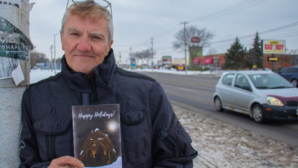 Andrew Swan posing with a Christmas card