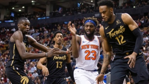 New York Knicks center Mitchell Robinson (23) is crowded out byToronto Raptors Chris Boucher (left), Malcolm Miller and Oshae Brissett (right) as he watches a loose ball during second half NBA basketball action in Toronto on Wednesday, November 27, 2019. THE CANADIAN PRESS/Chris Young